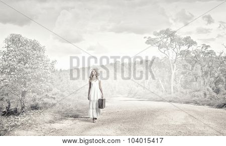 Woman with suitcase in white long dress and hat on forest road