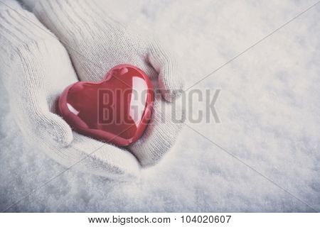 Female hands in white knitted mittens with a glossy red heart on a snow background.  Love and St. Valentine concept.