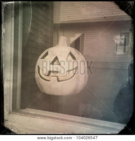 Halloween Jack o lantern sitting in a window sill - Instagram filtered