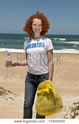 Volunteer Collecting Garbage On Beach