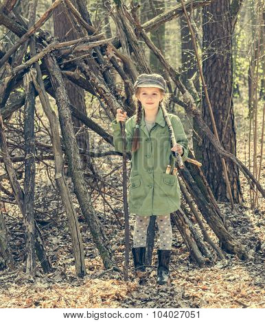 little girl in the wood near the hut. Photo in retro style