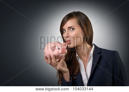 Successful Businesswoman Kissing Her Piggy Bank