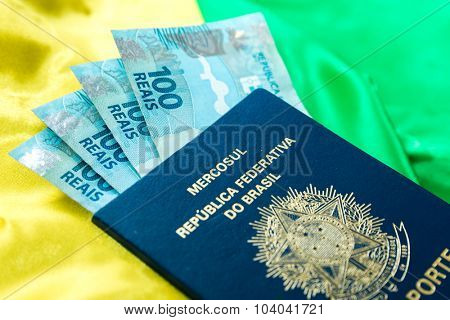 Brazilian passport and brazilian currency (100 Reais) on the table