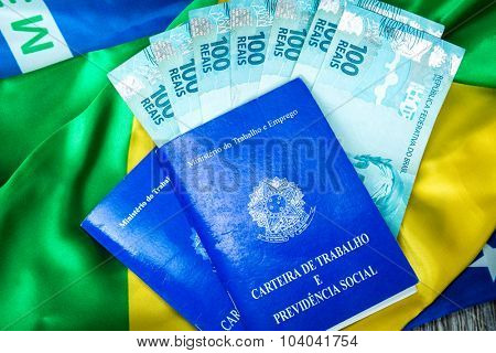 Brazilian work document and social security document (Portuguese: Carteira de Trabalho) and brazilian currency (Reais) on brazilian flag