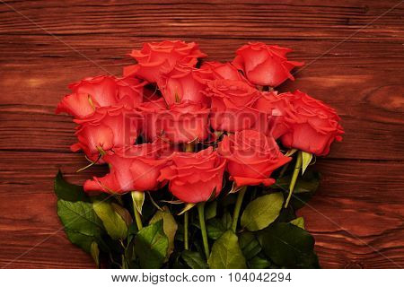 close-up photo of red roses on brown wooden background