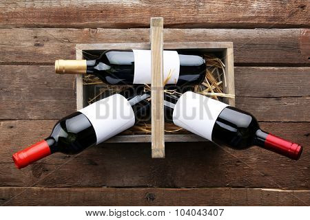 Wine bottles in basket on wooden background