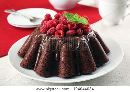 Tasty chocolate muffin with glaze and raspberries on table close up