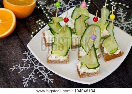 Appetizer Canape Sandwich With A Cucumber On A Wooden Table