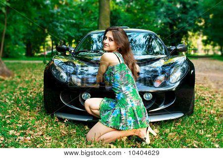 Menina bonita está sentado na frente do carro