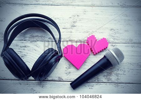 headphones and microphone on wooden background