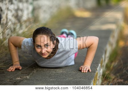 Young sports girl doing push-ups during the warm-up before Jogging in the Park. Healthy lifestyle.