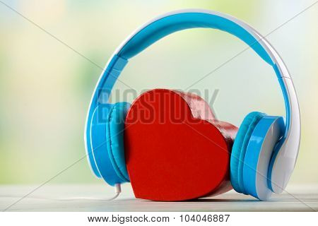 blue headphones with heart on unfocused background