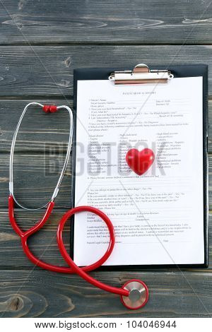 red rubber stethoscope with plastic heart and medical history on wooden background