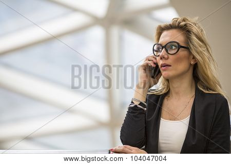 Young attractive business woman talks on the phone.