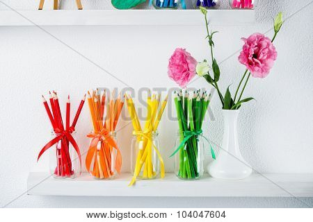 Bright pencils in glass jars on shelf