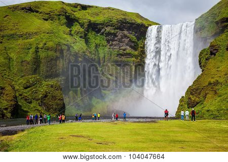 Magnificent famous waterfall Skógafoss, Iceland. A powerful jet Skógar river falls from a large glacier. Tourists delighted the crowd at the foot of roaring jets