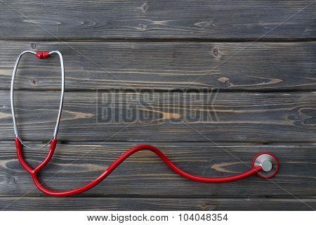 red stethoscope on dark brown wooden background