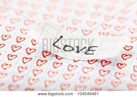 Word LOVE written on torn paper on heart background