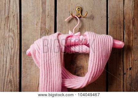 Pink scarf on hanger on wooden wall background
