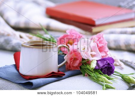 Cup of coffee with flowers near books on sofa in room