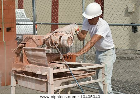 Worker Sawing Bricks