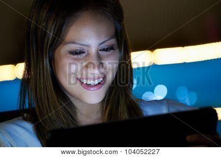 Latina Teenager Using Social Media On Tablet Pc At Night