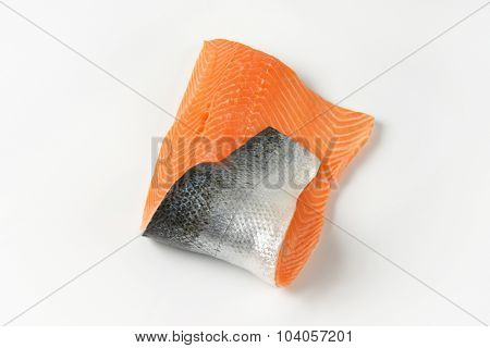 raw salmon fillet with skin on white background