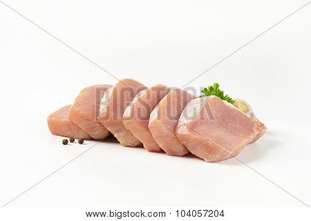 slices of raw pork tenderloin on white background