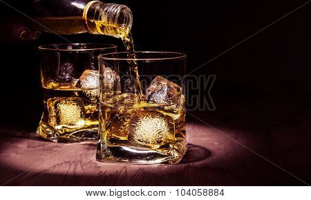 Barman Pouring Whiskey In The Glasses On Wood Table, Warm Atmosphere, Old Style, Time Of Relax With