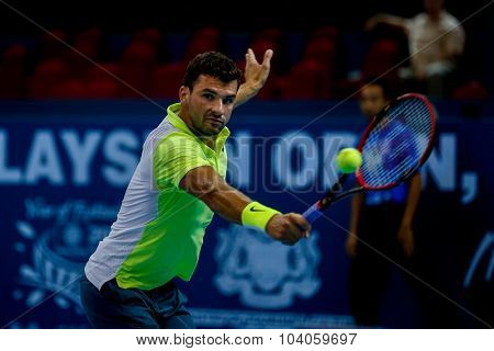 KUALA LUMPUR, MALAYSIA - OCTOBER 01, 2015: Grigor Dimitrov of Bulgaria hits a backhand return in his match at the Malaysian Open 2015 Tennis tournament held at the Putra Stadium, Malaysia.