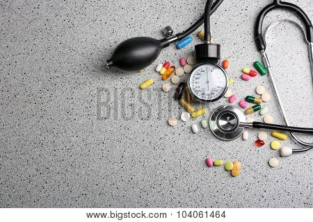 Blood pressure meter, pills and stethoscope, on grey background