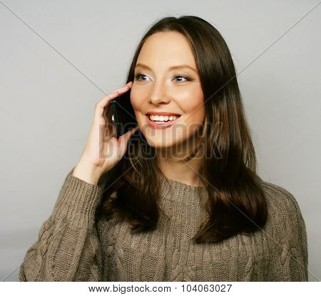 young happy woman using a mobile phone isolated on a white background