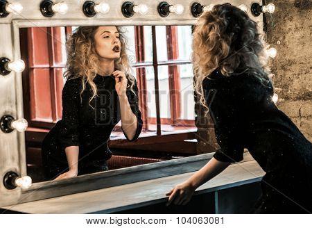 Beautiful fashion blond woman posing near the mirror
