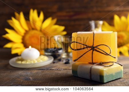 Soap bar and Spa treatments and sunflower on wooden background