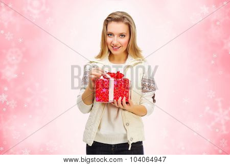 Young girl with gift box on red winter background