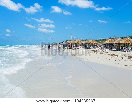 VARADERO,CUBA - OCTOBER 3, 2015 : Tourists relaxing and walking along the the beautiful beach of Varadero in Cuba