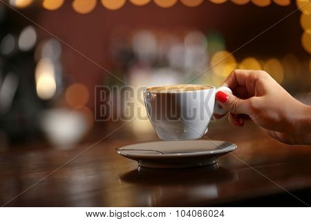 Female hand with cup of cappuccino on bar background