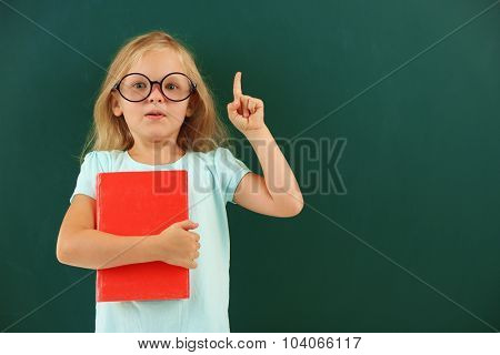 Beautiful little girl with book,  on blackboard background