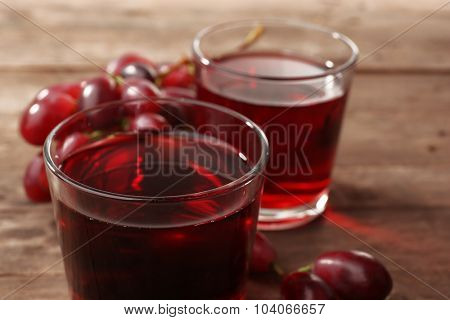 Glass of grape juice on wooden table, closeup