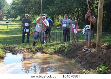 MUSKOGEE, OK - Sept. 12: Athletes try to avoid bloody zombies by jumping over a muddy pond during the Castle Zombie Run at the Castle of Muskogee in Muskogee, OK on September 12, 2015.