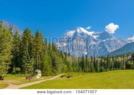 Scenery of high mountain peak over blue sky with white clouds and green foreground.