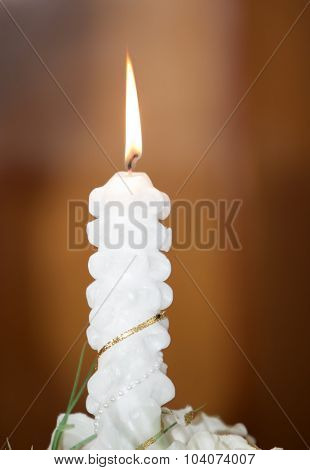 One Candle burning on a brown background