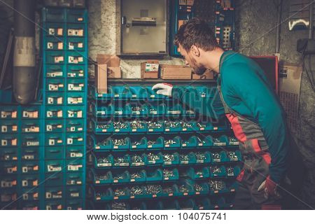Mechanic near shelves with bolts and nuts