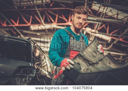 Mechanic with car bumper in a workshop