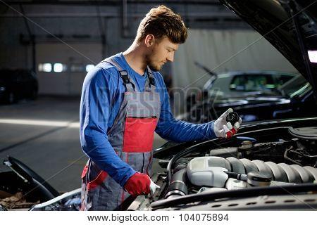 Mechanic with oil filling cork near open hood in a workshop