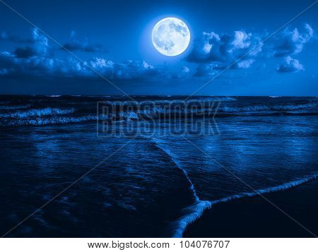 Beach at midnight with a full moon shining on the sky