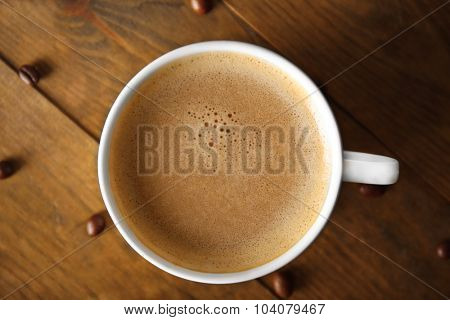 Cup of coffee with beans on wooden table, top view