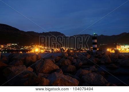 Night landscape with the image of beacon near Bar port, Montenegro