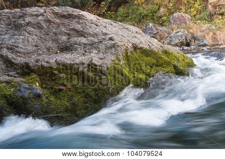 Mossy Granite Rock Ahainst Fast Flowing River