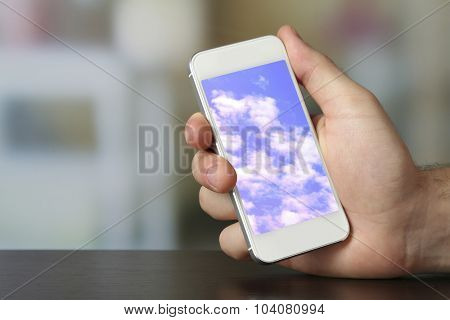 Hand holding mobile smart phone with sky in screen. Cloud computing concept